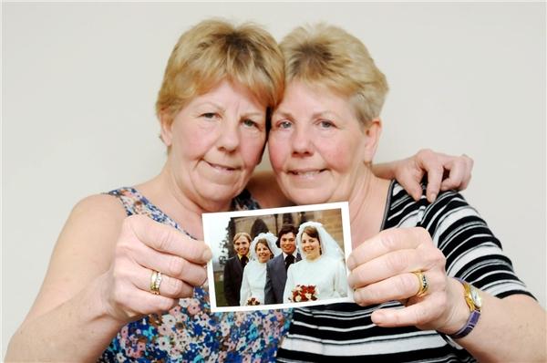 Bà Lynda (trái) và bà Ann cầm trên tay tấm ảnh cưới vài ngày sau khi hai người chồng mãi mãi ra đi. (Ảnh: SWNS)