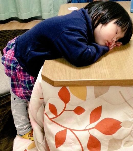 Lẽ ra phải để chân dưới bàn mới ấm, nhưng thế thì sẽ không nằm lên bàn được, nên cô bé tội nghiệp đành phải thế này thôi. (Ảnh: Internet)