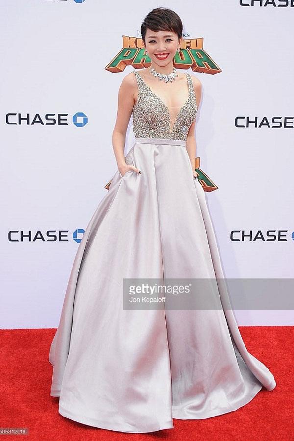 Sắc xám bạc cùng dáng váy xòe rộng giúp Tóc Tiên trông như nàng công chúa bước ra từ chuyện cổ tích trên thảm đỏ ra mắt phim tại Mỹ. Bộ váy có phom đơn giản trở nên nổi bật, thu hút hơn nhờ phần áo bằng chi tiết ánh kim.
