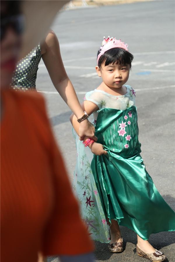 Trên nền sắc xanh ngọc lục bảo, những bông hoa màu tím hồng tạo thành điểm nhấn nổi bật cho bộ váy của cô bạn nhỏ này.
