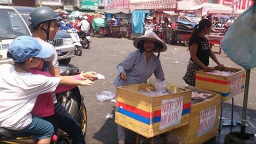 Cô Mười mang một lượt 3 thùng nước suối ra để phát cho du khách. Được biết cô đã phát gần 10.000 chai nước và 4000 ổ bánh mì trước chợ Thủ Dầu Một chỉ trong một buổi sáng. (Ảnh: Internet)