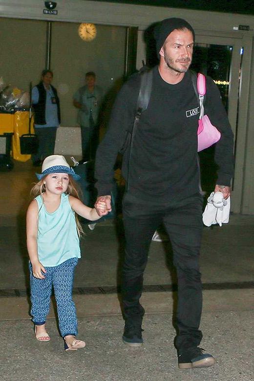 Harper mặc chiếc quần cùng tông với viền nón vàbố David đến sân bay LAX, tháng 7/2015. (Ảnh: Xposure)