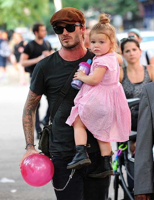 David bế bé Harper đang mang một đôi giày cá tính phối cùng một chiếc đầm hồngtại một sân chơi trẻ em. (Ảnh: Getty)
