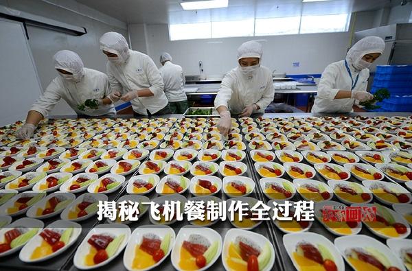 Các nhân viên công ty suất ăn hàng không đang miệt mài bày biện các món ăn.