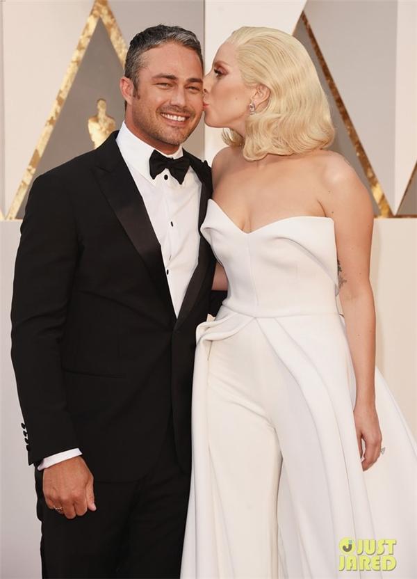 Nữ ca sĩ Lady Gaga không ngại ngần trao cho vị hôn phu Taylor Kinney một nụ hôn ngọt ngào ngay trên thảm đỏ. Năm nay, cô là một trong 5 người được đề cử ở hạng mục Ca khúc gốc hay nhất với Til it happen to you.