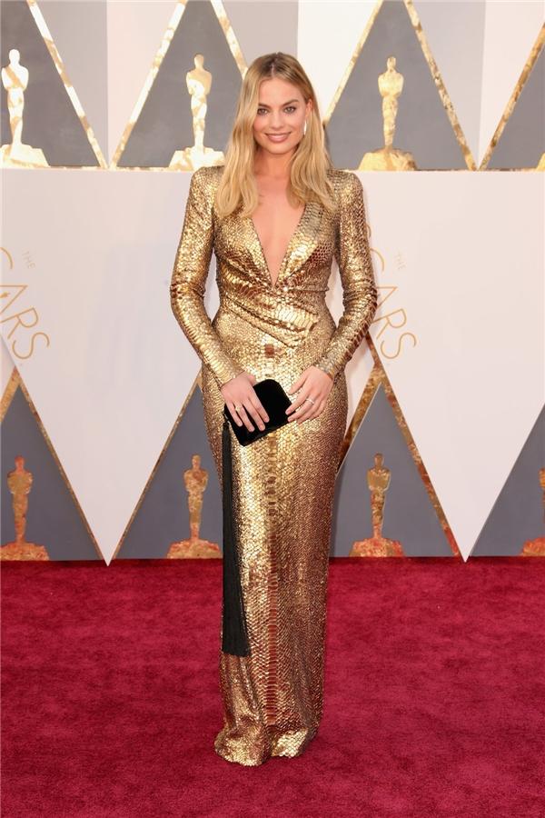 Dù diện chiếc váy có phom ôm sát gọn gàng nhưng Margot Robbie vẫn trở thành tâm điểm trên thảm đỏ Oscar lần thứ 88 nhờ chất liệu ánh kim nổi bật cùng đường xẻ ngực sâu hút.