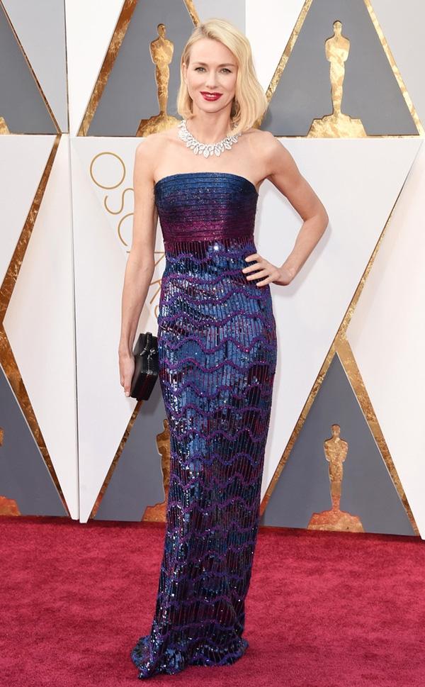 Naomi Watts tiếp tục minh chứng cho gu thời trang đỉnh cao của mình bằng thiết kế váy quây đơn giản trên nền chất liệu ánh kim với hiệu ứng chuyển màu liên tục.