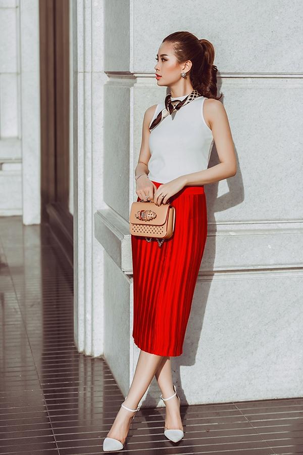 """Á hậu họ Nguyễn """"thắp sáng"""" đường phố bằng hai màu trắng - đỏ. Chân váy ôm giúp Diễm Trang khoe được đường cong gợi cảm. Cô sử dụng những phụ kiện tinh tế như hoa tai, nhẫn kim cương."""