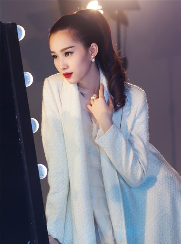 Hoa hậu Việt Nam 2012 thanh lịch, sang trọng với cả cây trắng. Tổng thể trở nên ấn tượng hơn nhờ chiếc áo khoác phom rộng với những đường cắt hiện đại, tinh tế.