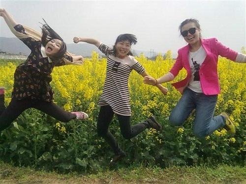 Ba cô gái nhảy nhiệt tình trước khóm hoa. (Ảnh: Internet)