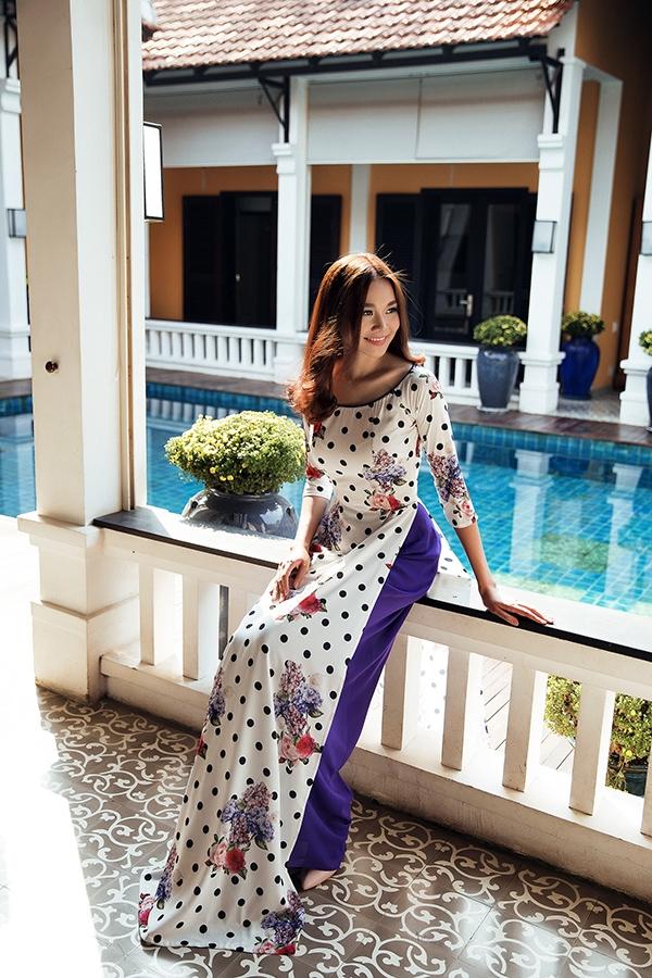 Cách diện áo dài nền trắng cùng quần lụa màu nổi khá được ưa chuộng trong những năm gần đây. Họa tiết hoa màu tím ngọt ngào hòa quyện với sắc tím thẫm ấn tượng trên nền lụa bóng mềm mại, nhẹ nhàng.