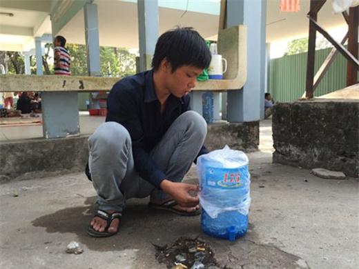 Anh trai của Bùi Hoàng Thiên Phươngđang dùng đá ướp bàn tay cho em.(Ảnh: VietNamNet)