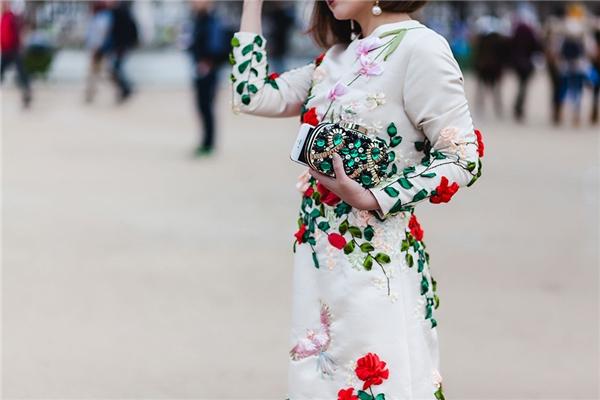 """Trâm Nguyễn phối bộ trang phục cùng chiếc clutch màu xanh ngọc sang trọng, quý phái. Cô cho biết: """"Góp mặt tại Tuần lễ Thời trang Paris lần này, Trâm mặc nhiều trang phục của các nhà thiết kế Việt khi tham dự show diễn. Trâm cảm thấy rất tự hào vì trang phục của mình được các nhiếp ảnh nước ngoài yêu thích, họ liên tục ghi lại những khoảnh khắc của Trâm trên đường phố Paris""""."""