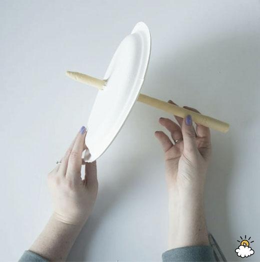 Sử dụng kéo cắt một lỗ nhỏ trên đĩa nhựa, rồi xuyên nến qua đó.