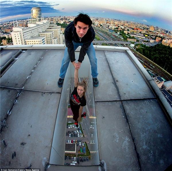 Semenov chụp hai người bạn mình đang tạo dáng hết sức thoải mái trên một công tchafngcao chót vót.(Ảnh: Daily Mail)
