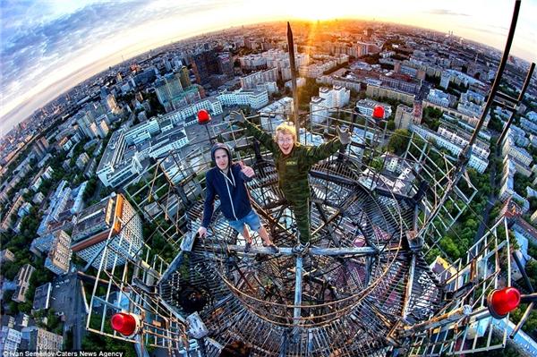 Các chàng trai đu mình trên một tấm ván mỏng nằm phía trên một tòa thápcao của thành phố Moscow, đằng sau là cảnh hoàng hôn tuyệt đẹp.(Ảnh: Daily Mail)