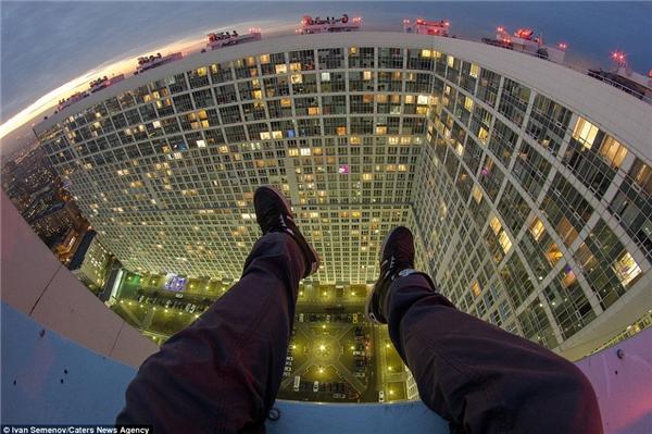 Bức ảnh chụp đôi chân của một kẻ liều lĩnh ngồi mấp mé trên bờ tường của tòa nhà cao tầng ở Moscow và trông ra đường chân trời.(Ảnh: Daily Mail)