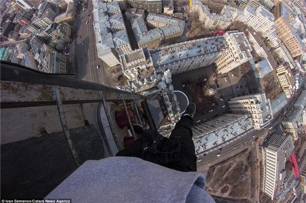 Sau một quãng đường dài trèo thang, anh chàng duỗi chân để thư giãn gân cốt, và hình ảnh vô tình giống như anh đang chuẩn bị bước giữa không trung.(Ảnh: Daily Mail)
