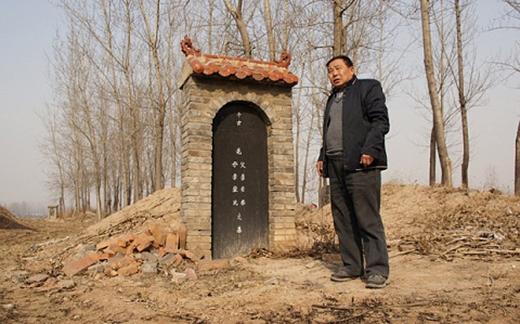 Một người đàn ông đang đứng trước ngôi mộ của mẹ ông đãbị đánh cắp xác.(Ảnh: Internet)