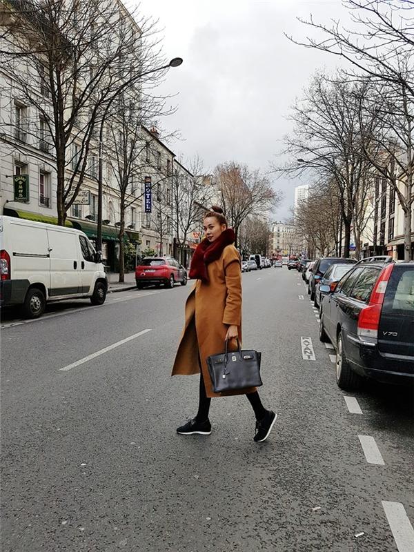Trên đường phố Paris lạnh giá, Thanh Hằng hóa thân thành quý cô cổ điển với áo măng tô to sụ kết hợp khăng choàng bằng lông trên nền những tông màu trầm, sang trọng, quý phái.