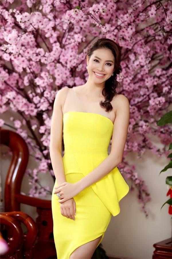 Phạm Hương ngọt ngào với tông vàng chanh trên nền dáng váy cocktail đơn giản, thanh lịch.