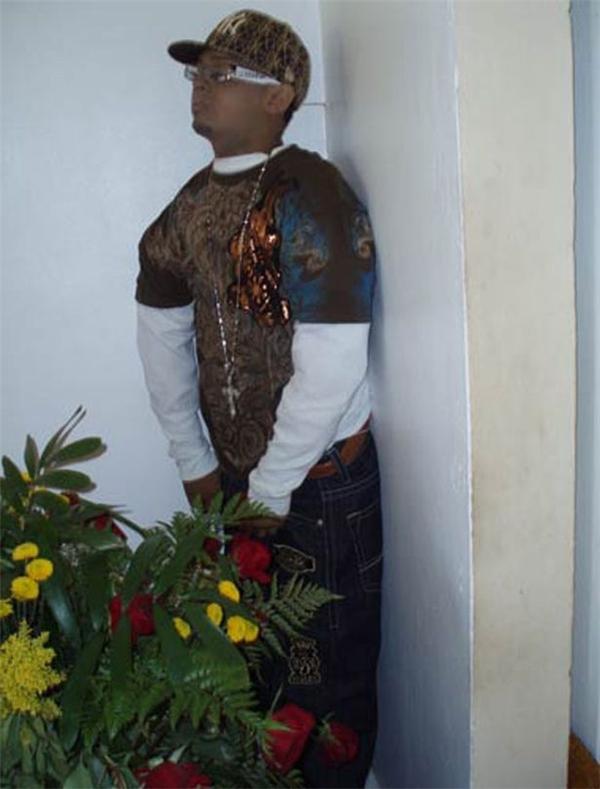 Angel Medina ăn mặc như một rapper và đứng dựa vào tường như quan sát đám tang của mình. (Ảnh: Internet)