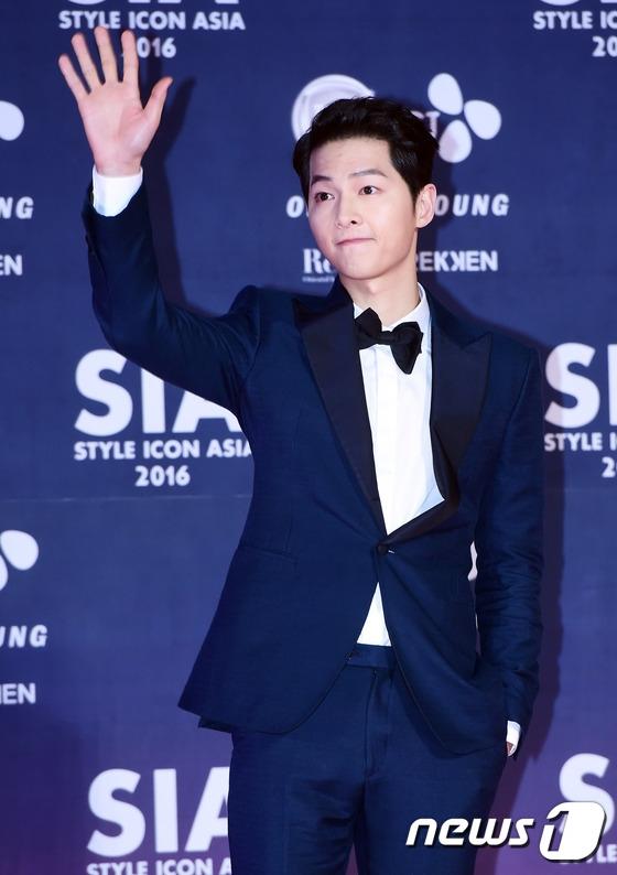 """Vẫn là gương mặt điển trai ấy, Song Joong Ki """"đốn tim"""" hàng loạt các fan nữ ngay khi vừa bước xuống xe, tiến vào khu vực thảm hồng. Đây là lần tham dự sự kiện đầu tiên sau họp báo Descendants of the Sun cách đây 1 tháng của nam diễn viên."""