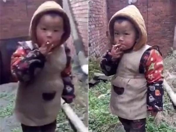 Hình ảnh cậu bé đứng hút thuốc, còn ông bố đứng cười khiến nhiều người bức xúc. Ảnh: Internet