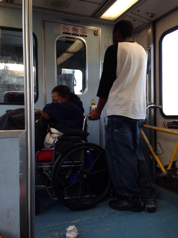 Một hành khách đứng vịn xe lăn. (Ảnh: Internet)