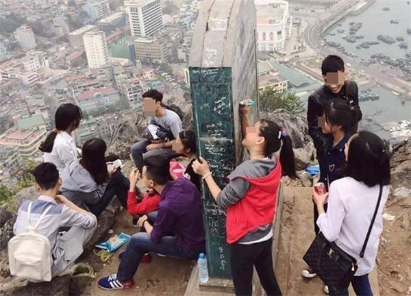 Nhóm bạn trẻ này viết bậy lên bia đá di tích lịch sử trên Núi Bài Thơ. Ảnh: Trần Văn Long.
