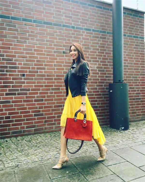 Trên đường phố Berlin, Hoa hậu Phạm Hương nổi bần bật với sắc vàng ấm áp, ngọt lịm. Kết hợp cùng dáng váy xoè giấu đường cong là chiếc áo khoác da tương phản phong cách.