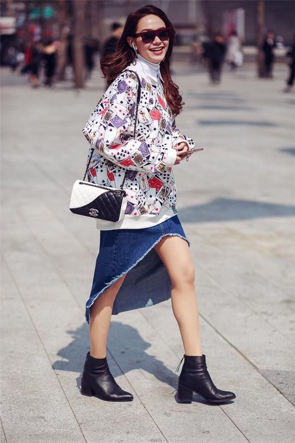 Gu thời trang của Minh Hằng trên đường phố Seoul nhận được nhiều lời khen bởi sự độc đáo, mới lạ. Nữ ca sĩ phối áo phông phom rộng hoạ tiết cùng chân váy denim có cấu trúc bất đối xứng hiện đại.