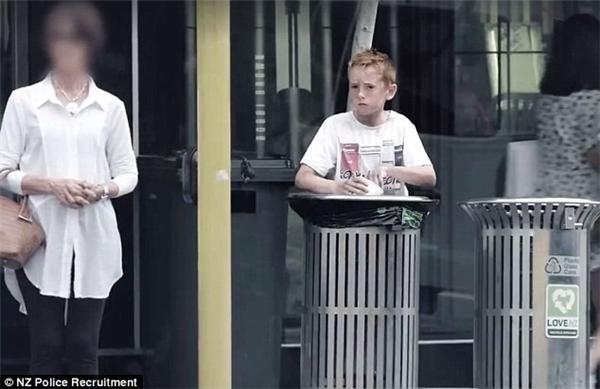 Cậu bé giả vờ làm người vô gia cư trên phố. Ảnh cắt từ clip.