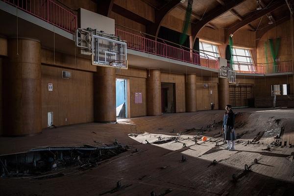 """Kanoko Sato đang đứng trong phòng tập thể dục của 1 ngôi trường ở Ukedo. Toàn bộ trường học đã bị thảm họa động đất sóng thần phá hủy. """"Nếu không có dự án ảnh của nhiếp ảnh gia người Pháp, có lẽ tôi sẽ chẳng bao giờ được tận mắt nhìn thấy cảnh tượng này. Dù sống ở Koriyama và rất gần với Ukedo nhưng tôi không hề biết rằng nơi mình từng gắn bó đã bị tàn phá đến nhường này"""", Kanoko nói."""