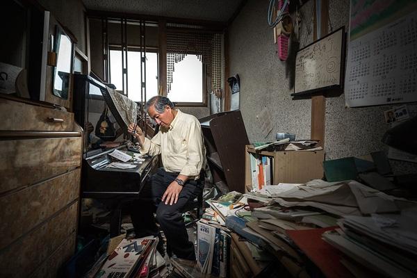 Ông Kazuhiro Onuki đang ngồi trong chính căn nhà của mình ở Tomioka. Trước khi thảm họa xảy ra, ông có 1 cửa hàng sách và cửa hàng đồ gốm Nhật Bản. Sau khi động đất sóng thần ập đến, cửa hàng của ông đã nhiều lần bị trộm ghé thăm, bởi vậy, những món đồ giá trị cũng dần biến mất. Căn phòng nơi ông ngồi chụp ảnh được giữ nguyên hiện trạng kể từ sau khi trận thảm họa kép xảy ra, phá hủy biết bao ngôi nhà. Hiện, ông Kazuhiro sống ở Tokyo cùng vợ và con gái.