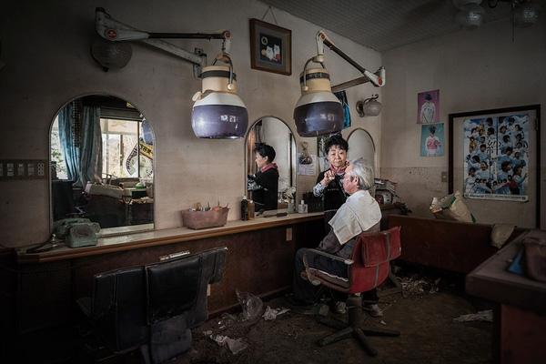 """Bà Hidemasa và ông Michiko Otaki đang ngồi trong 1 cửa hàng cắt tóc ở Tomioka, thị trấn bị ảnh hưởng nặng nề sau thảm họa động đất, sóng thần. Bà Hidemasa đã làm nghề cắt tóc được 40 năm. """"Khi vừa cắt tóc cho khách hàng xong, trận động đất đã xảy ra. Sau đó, chúng tôi phải sơ tán từ nơi này đến nơi khác. Tôi bắt đầu cắt tóc cho những người di cư có cùng cảnh ngộ với mình. Một hôm, 1 người di cư khác đã bảo tôi có 1 ngôi nhà cách nhà máy điện hạt nhân 40km, bởi vậy, tôi đã chuyển đến đó và ở suốt 2 năm qua"""", bà Hidemasa nói."""