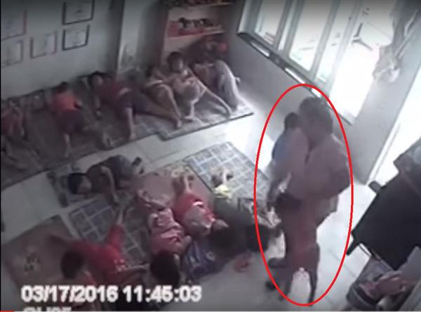 Một cô giáo tại trường mầm non Ngôi Sao Xanh (đường Huỳnh Tấn Phát, huyện Nhà Bè, TP.HCM) xách tay một cháu bé ném vào chỗ ngủ rồi quăng cặp, gối ôm vào người một bé khác. (Ảnh: Internet)