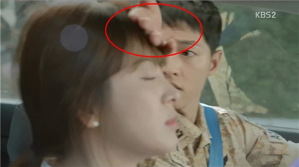 Yoo Shi Jin dùng mu bàn tay để đẩy Kang Mo Yeon ngồi sát vào ghế.
