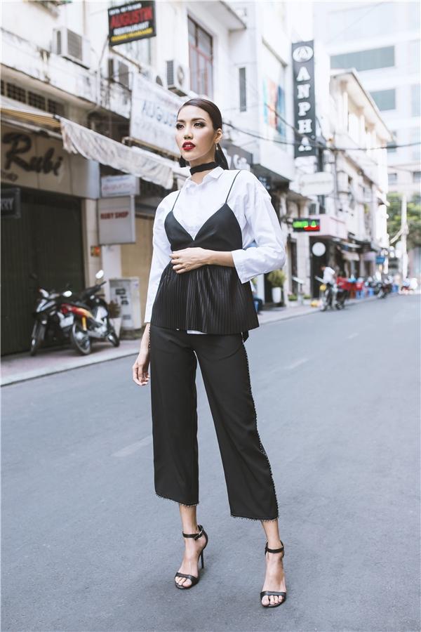 Gam màu đơn sắc trở nên bắt mắt hơn với cách tạo phom áo hai dây mặc ngoài sơ mi vô cùng đặc biệt.