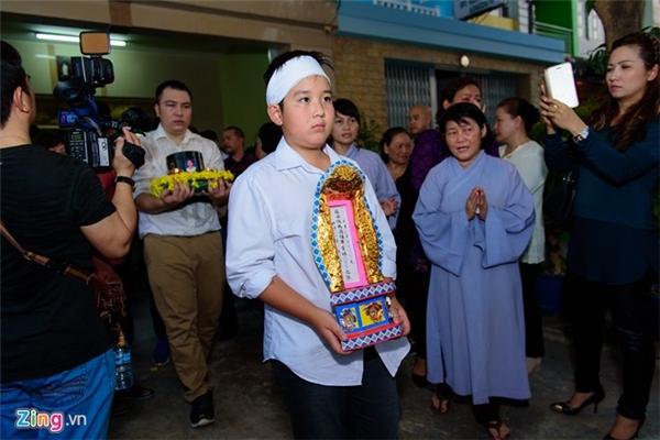 Con trai Quốc Hương ôm bài vị của ba trong tang lễ. Tro cốt của anh đặt tại chùa Di Lặc, quận Tân Phú, TP HCM.