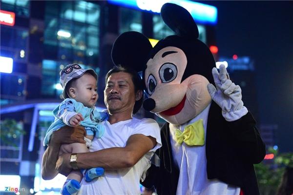 Bạn trẻ Nguyễn Viết Linh (ĐH Khoa học Tự nhiên, ĐHQG TP HCM) trong vai chuột Mickey vẫy tay chào em nhỏ. Linh cho biết, hàng ngày bắt đầu làm công việc này từ 18h đến khoảng 22h30. Mỗi ngày, nam sinh này kiếm được khoảng 100.000 đồng nhờ việc đóng giả thú bông bán kẹo.