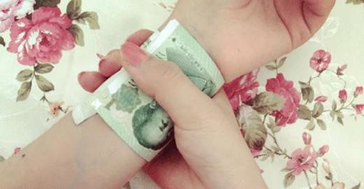 Thiếu nữ Trung Quốc rộ mốt dùng tiền đo cổ tay thon