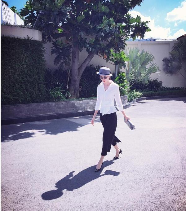 Hoa hậu Thu Thảo lại như một nàng tiểu thư yêu kiều khi diện sơ mi cách điệu thắt nơ phần eo và quần culottes. Người đẹp không quên kết hợp cùng đôi cao gót đen và mũ để hoàn thiện nét nứ tính, duyên dáng trong phong cách của mình.