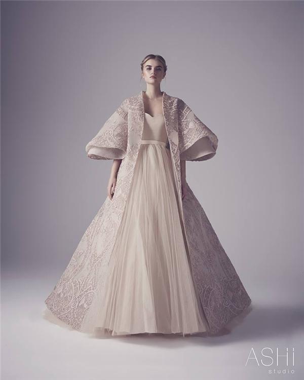 Thiết kế kết hợp giữa sự mềm mại của dáng váy xoè cổ điển cùng những đường nét hiện đại, sắc sảo của dáng áo choàng đặc trưng phương Tây.