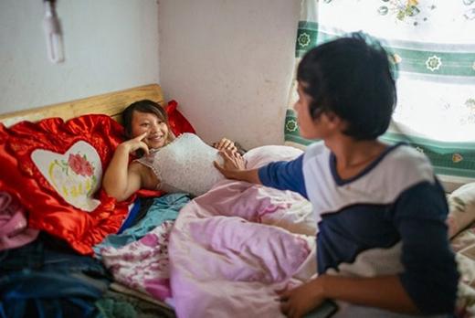 Wen, 18 tuổi, đang chạm vào bụng vợ để cảm nhận những chuyển động của đứa trẻ đang lớn dần. Cặp vợ chồng sống ở làng Tangzibian, huyện Mãnh Lạp, tỉnh Vân Nam, và kết hôn chỉ 3 ngày sau khi gặp nhau vào năm 2014.