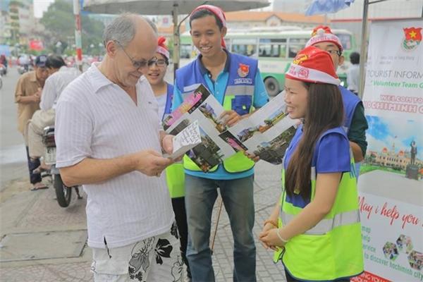 Các tình nguyện viên với nụ cười trên môi và câu hỏi 'Tôi có thể giúp gì cho bạn?' sẵn sàng giúp đỡ du khách nước ngoài tại TP HCM. Ảnh: Quang Minh.
