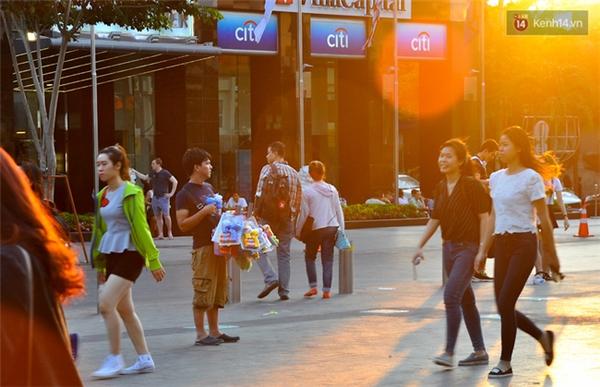 Nam thanh niên lủng lẳng đồ chơi đứng mời người dân đi bộ.