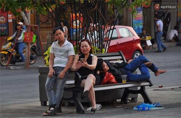 Nam thanh niên nằm dài trên ghế trong chẳng cho ai ngồi nữa và rác cũng đầy dưới chân.