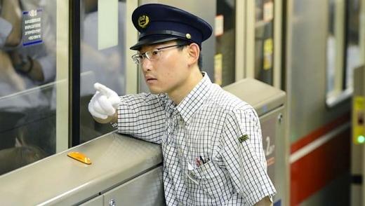 Một kiểm soát viên tại trạm chỉ huy ra hiệu lệnh đóng cửa tàu để chuẩn bị khởi hành.