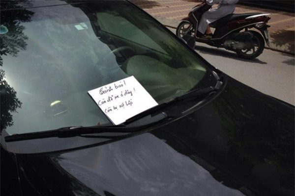 Một số người chọn cách xịt lốp xe và để giấy cảnh cáo không cho chủ xe tiếp tục đỗ xe. (Ảnh: Internet)